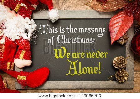 Blackboard with the text: This Is The Message of Christmas: We Are Never Alone!