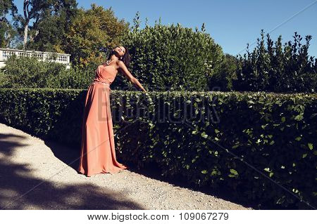 beautiful mulatto girl in coral dress posing in park