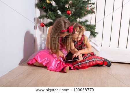 Two Little Sisters Using The Tablet Pc