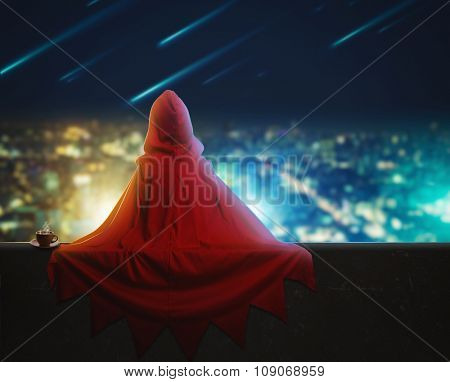 Super hero girl sitting on a high building over the evening city
