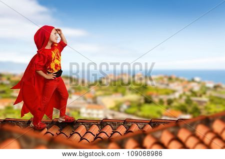 Little girl in a superhero costume standing on the roof