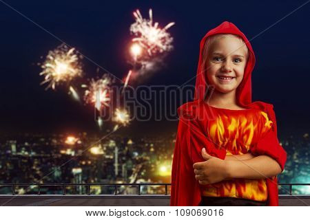 Little girl in masquerade costume in the evening street over the firework