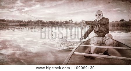 senior paddler enjoying paddling a canoe on a calm lake at sunset, a grunge texture finish in sepia tone