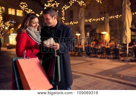 Smiling couple checking shopping list for Christmas on decorated car-free street