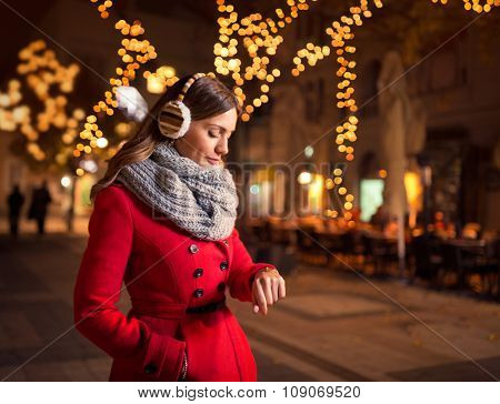 woman looking at her watch in street while waiting her boyfriend who is late for a date