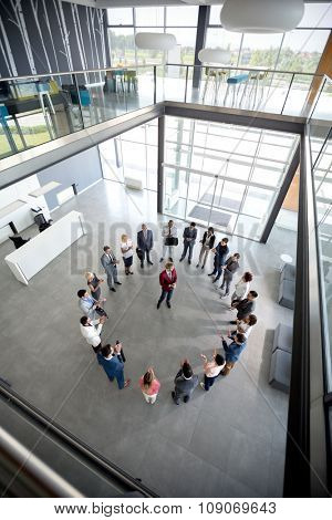 Top view of businessman with team in circle in company hall