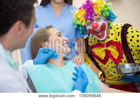 Colorful fanny clown in dental clinic draws attention to young girl