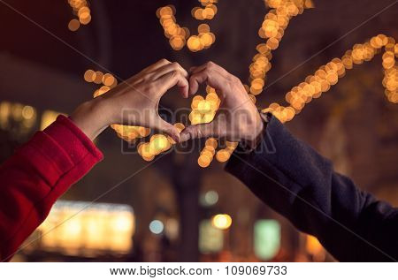couple making heart shape with hands over the Christmas illumination
