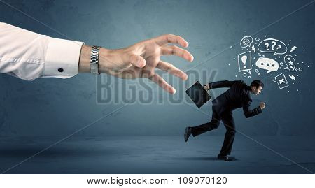 Business man with doodle icons running from a big hand concept on background