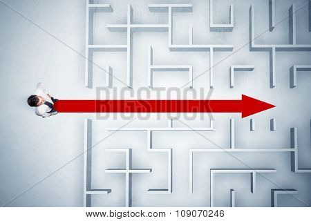 Business man looking at maze with red arrow showing the path