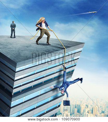Woman standing on the roof a high building is rescueing a businessman with the rope