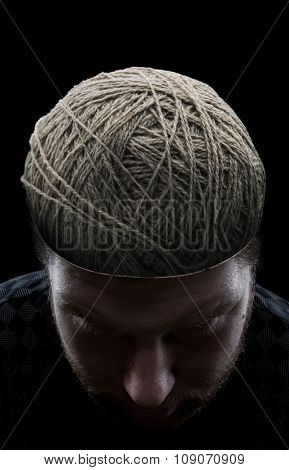Young man with closed eyes and with balls of yarns instead of his brain