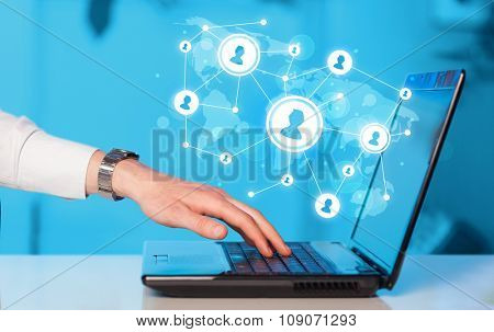 Close up of hand with laptop and social media network icons