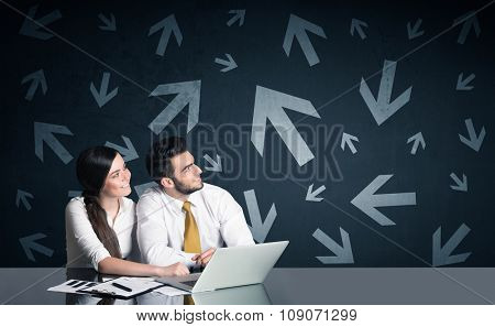 Successful business couple with arrows in background