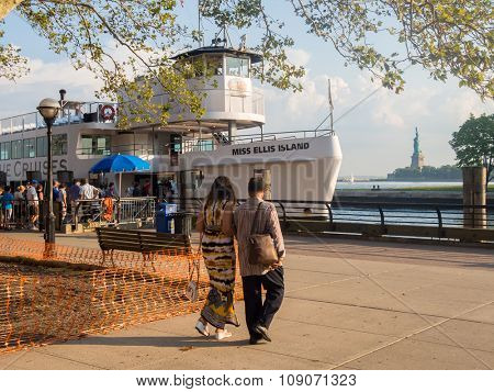 NEW YORK,USA - AUGUST 16,2015 : Tourists boarding a ship at Ellis Island with the Statue of Liberty on the background