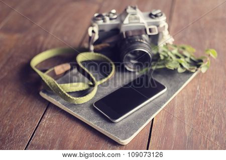 Vintage Camera, Blank Smartphone, Diary And Leaves On Wooden Table