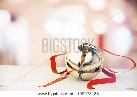 Jingle Bell With Red Ribbon On White Table