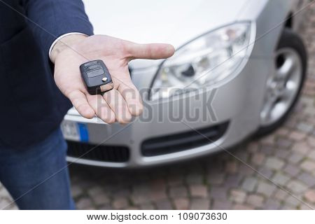 man hand with car in background holding a automobile key