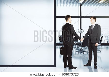 Business Partners Shake Hands In Modern Conference Room With Blank White Wall, Mock Up