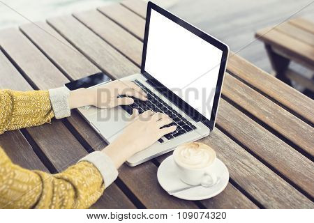 Typing Girl With Blank Laptop Screen, Smartphone And Cup Of Coffee On Wooden Table Outdoor, Mock Up