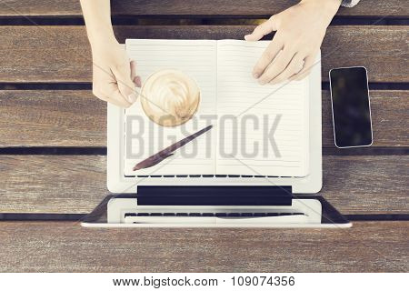 Girl With Laptop, Coffee Mug, Blank Diary And Cell Phone On Wooden Table