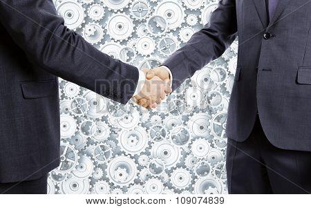 Businessmen Shake Hands At Cogwheels Background