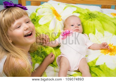 Five-year Girl Joyfully Laughs While Holding The Handle Of A Newborn Baby