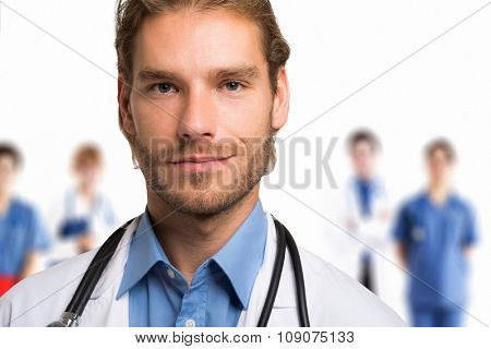 Portrait of a smiling handsome doctor in front of his team