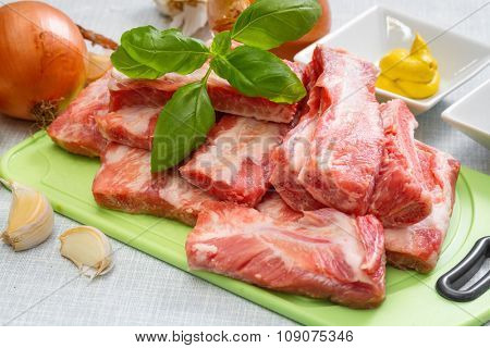 Raw pork ribs on a cutting board and  set of spices for cooking. Step on step recipe.