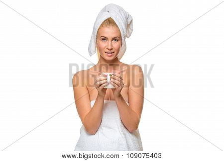 Young attractive woman in towel holding a cup