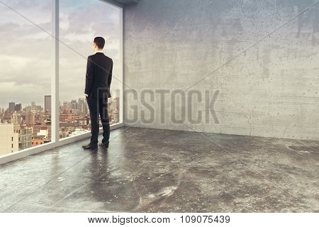 Businessman In Empty Loft Style Office With Windows In Floor