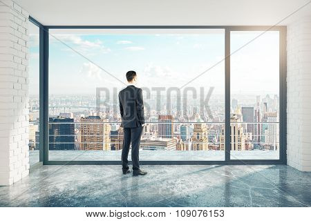 Businessman In Empty Loft Room With Big Window In Floor And City View