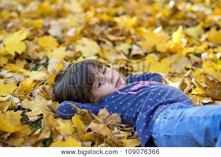 little girl lying on the yellow leaves in the autumn park
