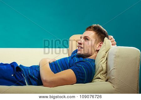 Young Man Relaxing On Couch On Blue