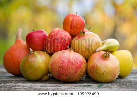 Fresh autumn fruits, apples, pomegranate and banana, on a wooden table