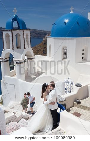 A Couple Of Newlywed's Tourists In Front Of Church With The View Of Santorini Island, In Greece. Tou