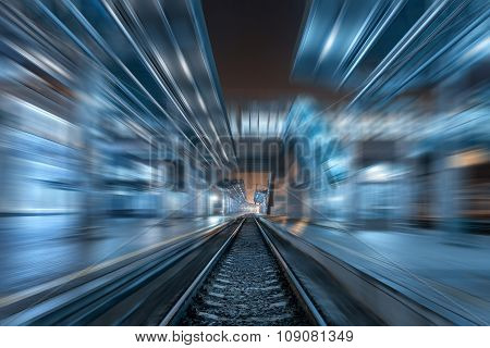 Railway station at night with motion blur effect. Cargo train platform in fog. Railroad