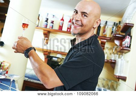 Portrait of sommelier holding a little wine glass with aperitive alcohol drink