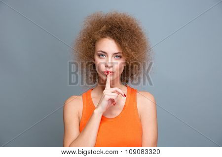 Beautiful curly woman showing silence sign with forefinger near lips on gray background