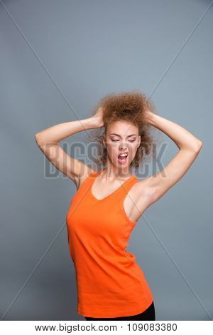Amusing funny confident emotional young curly woman in orange top posing, playing with hair and making a grimace