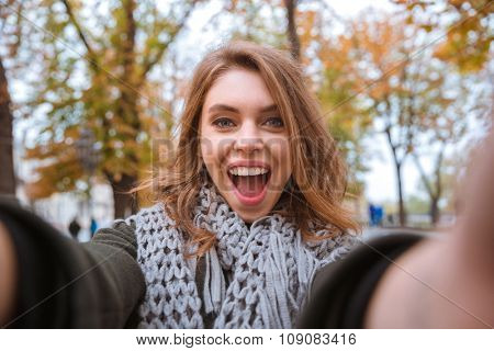 Portrait of a laughing woman making selfie photo in autumn park