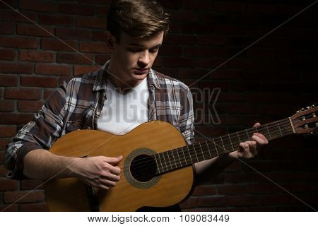 Attractive handsome shy young guitarist in checkered shirt playing acoustic guitar