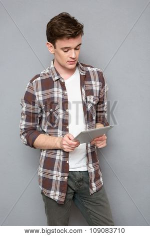 Portrait of a young casual man using tablet computer on gray background