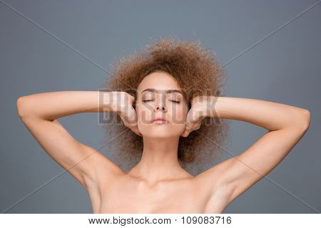 Closeup of young sensual seductive relaxed natural young woman with eyes closed covering ears by hands