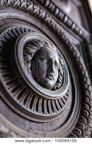 Detail of vintage wooden door with hand-carved head of a woman