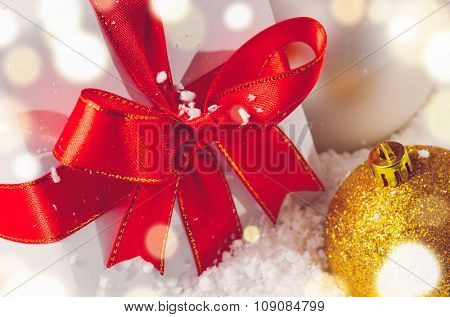 white decorative christmas gift box with ribbon and balls on snow, view from above