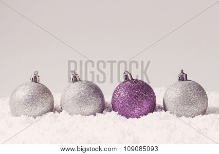 silver and purple decorative christmas balls on snow against grey background
