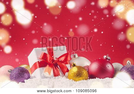 white decorative christmas gift box with ribbon and balls on snow against red festive background