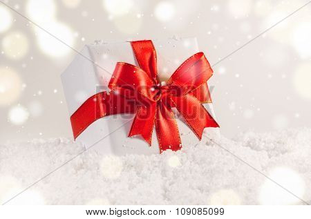 white decorative christmas gift box with red ribbon on snow against grey festive background