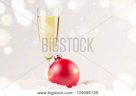 red decorative christmas ball on snow against grey festive background with glass of sparkling wine